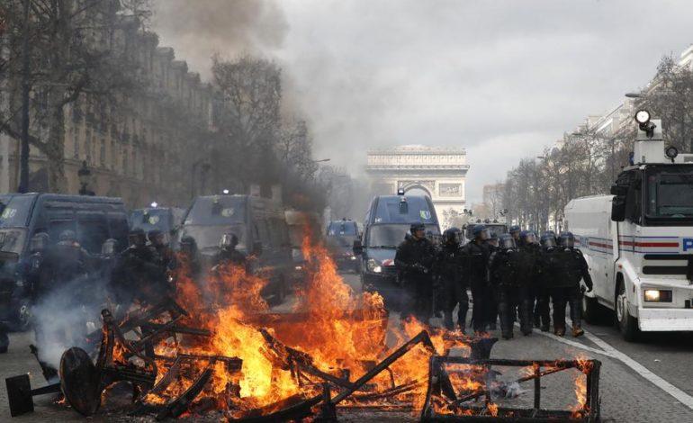 Parigi, Gilet gialli in piazza: scontri e saccheggi, in fiamme un palazzo, 11 feriti