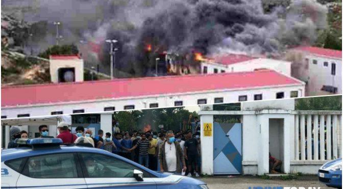 Immigrati in rivolta incendiano la caserma dove sono ospitati e fuggono da quarantena (Video)